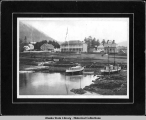 Sitka waterfront with two boats and Marine Corps barracks, ca. 1900.