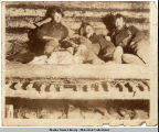 Three men relax on their cabin bunk, ca. 1898.