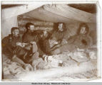 Four prospectors relax on their cabin bunk, ca. 1898.