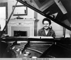 First Lady Neva Egan plays piano in Governor's Mansion, Juneau, 1962.