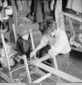 Children helping father with a sled being built in the cabin, Minto, 3/39.