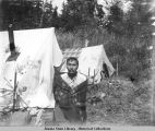 Man standing near tents.