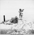 Hunter looking for polar bears from atop his igloo, Point Hope, 3/1942.