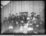 Group portrait of men, women and children in front of building.