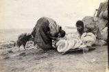 Chukchu women at Whalen, inflating walrus intestines, 1917.
