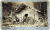 Family group in front of log cabin in Southeast Alaska.