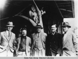 Wiley Post, Rex Beach, Joe Crosson, Will Rogers at airplane hangar in Juneau.  August 1935.
