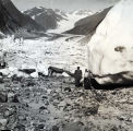 Shell Simmons, in pilot uniform, standing at foot of glacier.