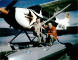 Shell and Bee Simmons pose on their Cessna 185 on floats.