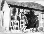 Animal skins displayed on outside wall of house.