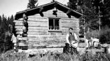Ted Pedersen outside a log cabin.