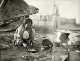 Native woman, cooking outside, ca. 1906.