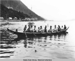 Indian dugout canoe in front of Auk Village, Juneau with 16 men and a boy.