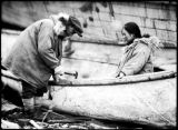 Native man and woman, working on canoe.