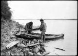 Two men with wooden canoe.