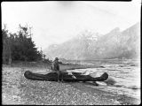 Man with canoe on lake shore.
