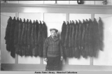 Man in cap and plaid coat standing with animal pelts strung on wall.