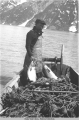 Man holding two salmon in small boat filled with net and floats.