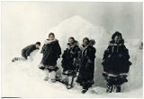 Nome women in fur parkas pose in front of snowbank.