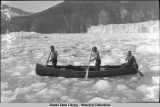 Three men paddling canoe in ice before Taku Glacier.