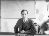 Bartlett L. Thane seated at desk in office.