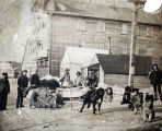 Men on street, with dog teams and sleds.