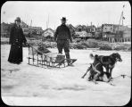 Couple with loaded sled and dog team, Nome, Alaska.