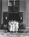 Eight nurses and two men in front of the main entrance to St. Ann's Hospital, after 1936.