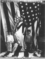 Tableau; girl and two boys with flags. c. 1902.