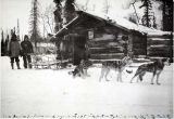 Fred B. Dodge and two other men outside cabin.