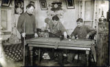 Three men shoot billiards in house, ca. 1910.