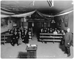 Rev. F.L. Forbes, D.D., holding services in Moose Lodge, Long, Alaska, Jan. 6, 1918.
