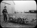 Eli Smith, next to dog sled on wheels, ca. 1907.