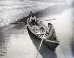 Athabaskan parents and child in rowboat on Koyukuk River.