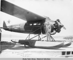 An Alaska Washington Airways Pontoon plane on the dock with a young man posed on one of the...