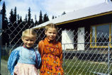 [Close-up of 2 young girls in front of a link fence; house beyond.]