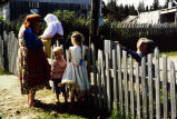 [Adults and children standing near a white picket fence.]