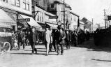 [Men marching in a parade, downtown Juneau, ca. 1918.]