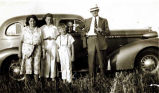 [Five people standing next to a car, ca. 1930's.]