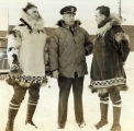 [Fr. Bernard Hubbard, SJ, (r.) stands in parka with another man in parka and a naval officer.]