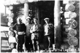 "[Crew members of the dirigible ""Norge"" in doorway of a log cabin.]"