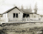 [One story wooden house; white picket fence.]