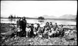 [Group of women and children sitting along rock beach.]