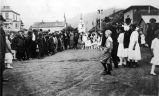 [Francis Barron (center background, holding bag) at 4th of July activity, Sitka, ca. 1915 (verso).]