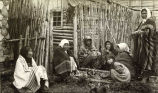 Chilkat Indians sitting near log home.