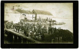[Wharf at Sitka 1889? filled with people.  Buildings in background.]