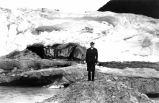 [Man in uniform standing in front of glacier.]