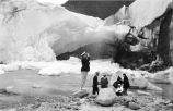[Six people at shoreline below glacier (probably the Mendenhall Glacier).]