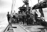 [Nineteen men posed on deck of ship.]