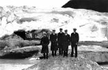 [Five men in uniform standing in front of glacier.]